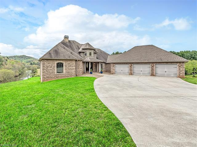 Special & rare setting with 600 ft. of French Broad River frontage. Beautiful mountain views on 19.92 acres &  adjoins 146 acres of conservation.Custom brick 4 bedrooms/4.5 baths with views from every room. Spacious master suite with office, fireplace & private covered porch overlooking the river. 2 Story great room with walls of windows & see through fireplace. Attached 3 car garage & 4 car detached with bathroom & storage. Great outdoor decking with gazebo for entertaining.More land available