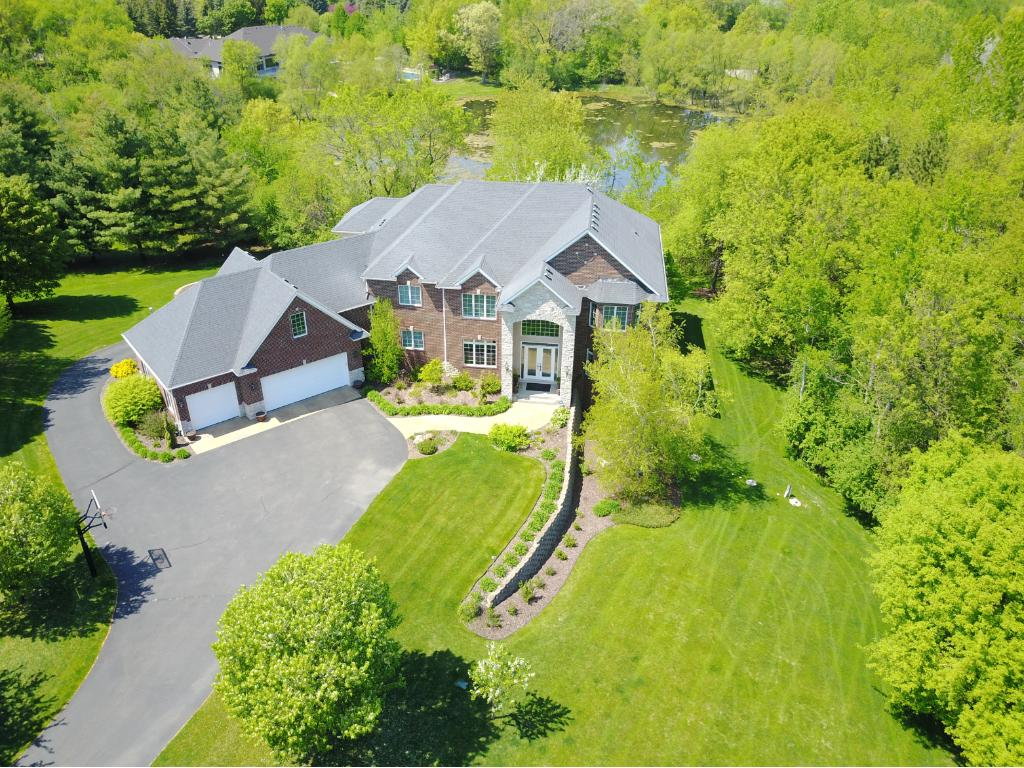 Remarkable custom built home situated on a private 4+ acre lot with pond views. Open design flooring plan w/20' vaulted great room. Gourmet kitchen w/granite & high end SS appl's. 4BRs up incl master suite w/private sitting area, dual walk-in closets & bonus rm. Huge walk-out LL w/full wet bar & rec rm. Maintenance free decks & stamped concrete patio. Central vacuum system, built-in surround sound, tons of storage & security system. Sprawling heated 6-car garage w/rear garage door.