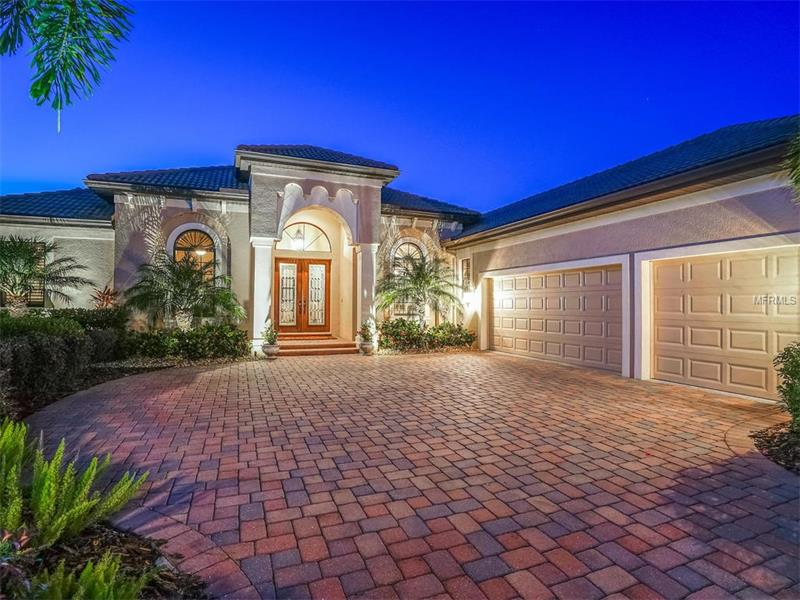 This exquisite John Cannon residence complimented with lush landscaping and private gardens, situated in the LaCantera neighborhood of the Lakewood Ranch Country Club, is truly one to marvel. Architectural details abound with incredible custom moldings and columns, gorgeous 7.25-inch plank wood floors and beautiful, built-in fireplace. Step out through either set of sliders to see the enchanting outdoor area with large covered lanai, saltwater pool, outdoor kitchen and park-like setting, perfect for entertaining while enjoying the spectacular view. The fenced back area is a highly sought-after, yet rarely found, private sanctuary. The large, newly upgraded gourmet kitchen includes exotic granite countertops, wood cabinetry, stunning oversized island and stainless steel appliances including five-burner Wolf cooktop. The master retreat with separate walk-in closets and lavish master bath creates the perfect oasis. Other notable features include a three-car garage, separate office, large bonus room and two guest suites as well as impact windows throughout. The Country Club features two Arnold Palmer-designed golf courses, private Country Club, fitness center, 18 lit tennis courts, two pickleball courts and playground. If you are impressed by detail and luxury, then this very special home is one you will truly want to see.
