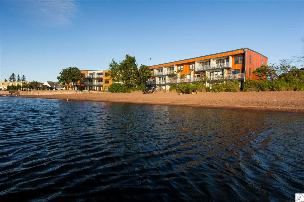 This lovely condo is located on the 1st floor and offers a sliding glass door to patio with easy access to the Lake Superior Beach.  Also featuring a deck for morning coffee .  With a full kitchen, two fireplaces, Living room with large windows, listen to the waves lap the shore, watch the sunrise over the lake, or the moonlight shine across the water from the Living Room or Bedroom.  This is a corner unit condominium offering extra windows and patio doors.   In the heart of Grand Marais: shops, restaurants, walking trails and the famous Lighthouse Point is right out your door.   Call today for a showing.
