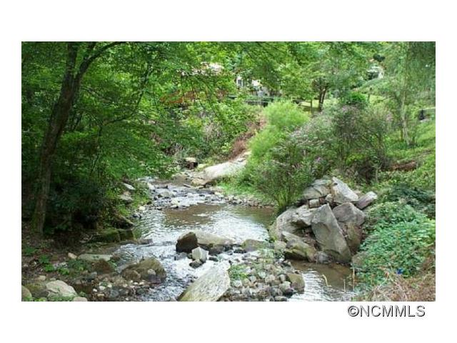 1 acre unrestricted lot on a beautiful, BOLD rushing mountain stream in the Bat Cave area.  Cleared and with septic in place, ready to build on or move a mobile home on. Near Chimney Rock and Lake Lure on a paved road.