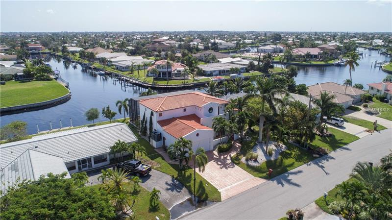 Spectacular custom executive home located in the desirable deed restricted community of Punta Gorda Isles. This light and bright home offers IMMEDIATE SAILBOAT ACCESS to Charlotte Harbor and on to the Gulf of Mexico. 80 foot concrete seawall and 30 foot concrete dock with water and electric. **FABULOUS LONG CANAL VIEW** This spacious two story home features 4 Bedrooms, 3 full Bathrooms and two half baths. On the first floor there is a Great Room, separate Dining Room, well appointed Kitchen, Office/den with wet bar and Inside Laundry. The Kitchen features wood cabinets, granite counters, breakfast bar and Mexican tile flooring. There is a half bath off the laundry room. There are TWO master bedroom suites, one on each floor. The Master Bedroom on the first floor has a full bathroom, walk in closet. The Master BR on the second floor has a large sitting area, full bathroom with dual sinks, tub, separate shower, bidet, TWO walk in closets and adjoining office. Two guest bedrooms are on the second floor and the guest bathroom has a tub/shower combo. There is also a loft entertainment area with wet bar, screened lanai and balcony. There are tile floors throughout the home, two hot water heaters (2014 and 2016) TWO A/C units (2012), hurricane resistant windows, doors and sliders (2014), water softener 2015, inground sprinkler system, landscape lighting, security/fire alarm system (2014)  Your living space extends to the heated saltwater pool with high efficiency pump. Outdoor shower. SO MANY MORE UPGRADES!