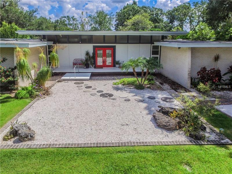 Mid-Century Modern home on over 1/2 acre designed by Frank DePasquale! Incidentally, much of the home's original, phenomenal design was left intact by homeowners who appreciated the structure's many well-thought-out details. The indoor-outdoor meld plays out in this modern house, which contains 4,200 sf under roof, via a raised, covered patio and a giant wall of glass sliders that creates a river-view lookout area from nearly every room. The master bedroom, too, offers floor-to-ceiling views of the backyard, pool and Hillsborough River on 2 separate walls. The home's front sports a unique cantilevered porch that jets out from the bottom of the house suspended in air. Its location – situated on the widest part of the Hillsborough River – cannot be replicated. Take a 9-mile cruise to one of the crown-jewel parks in the region, Lettuce Lake. Many islands can be spotted along the way, complete with osprey-nest-topped trees. A new wooden dock w/ lift can house a 20' boat and there's a concrete boat/RV carport. A primary pleasure of living in a mid-century home is the way the separation between indoor and outdoor space is made all but invisible. Even the steps leading to the back patio create a touch of drama and also signal another tip off to the mid-century design: lavish use of organic materials, including block, brick, stucco, and wood. Extras: large bonus room with AC could be an artist's studio, water-treatment system, upgraded electrical. What's not to love in this fabulous, lifestyle-enhancing home.