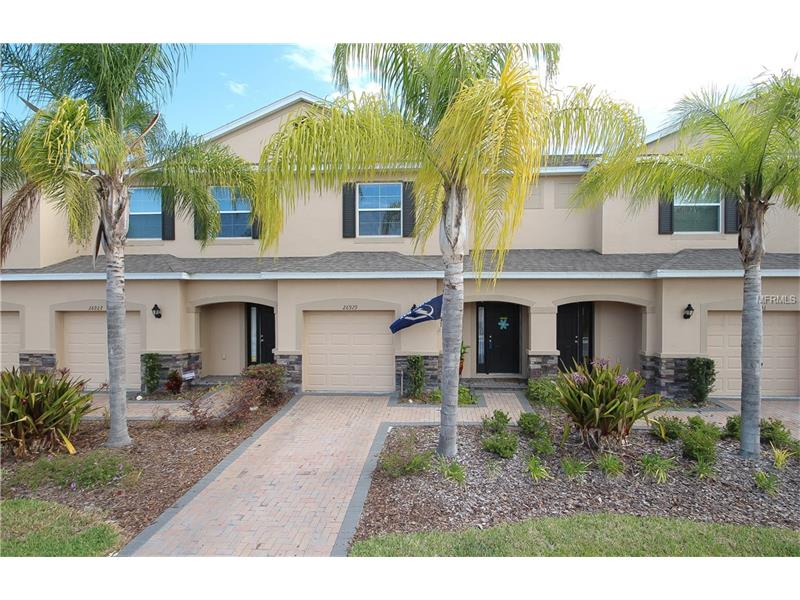 """Immaculate 3 bedroom, 2.5 bath townhome with 1 car garage located within the gated community of Lakeside at Seven Oaks!  The """"Cedar"""" floor plan offers an open, bright living area with beautiful tile flooring in all the wet areas, to include the foyer, kitchen, laundry room, all bathrooms and extended tile throughout the main living room.  Well maintained and neutral carpet covers the stairwell, upstairs hallway and bedrooms.  A beautiful and updated kitchen offers recessed and decorative pendant lighting, cherry wood cabinetry with crown molding, all stainless-steel appliances included, granite countertops, wrap around breakfast bar, and eat in dining area overlooking the outdoor covered patio!  The master suite is a must see, very spacious in size.  The master bathroom includes granite countertops, dual vanity, and walk in shower.  Generous in size, secondary bedrooms offer partial pond view, full bath with shower/tub.  Attached lighting fixtures, ceiling fans, washer & dryer, and attached shelving ALL convey with the home.  Enjoy your weekends poolside at the community clubhouse with state of the art amenities to include: cabanas with two pools, waterslide, kids splash zone, covered tot lot and park, sport courts, clubhouse with business center, café, movie theatre and fitness!  Great location, with easy access to I-75, local dining/shopping with Wiregrass Mall, Tampa Premium Outlets and more."""