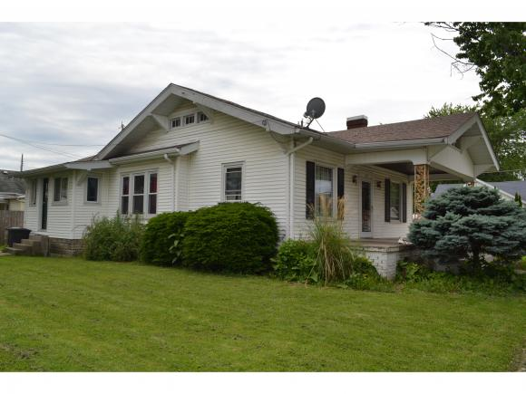Home with lots of character and charm.  Hardwood floors and beautiful oak trim.  Large living room with gas log fireplace; dining room, kitchen with breakfast nook, 2 bedrooms and 1 full bath. Covered front porch, basement, 2 car detached garage on a .16 acre corner lot in town.  Convenient to churches, shopping and restaurants. Newer items are roof on garage and hot water heater.