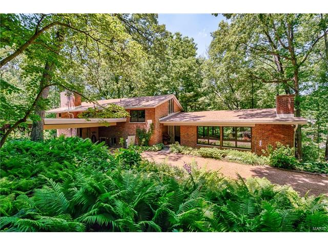 In the heart of Ladue is this special Mid-century custom designed home set on a private, wooded lot of 1.63 acres. The home is perched on the top of a hill & has serene views of the old-growth wooded valley.  You enter the home into a dramatic Living Room with a wall of floor to ceiling windows, beamed vaulted ceiling & a fireplace.  The kitchen level features an open floor plan with a Dining Room, Family Room with fireplace, a full bath & plenty of light streaming in from all of the windows. Upstairs is a master suite with an ensuite bathroom & private den featuring a fireplace. There are 3 additional bedrooms & 2 more bathrooms on this level. A long balcony runs along the home that you can access from the upper level. You will love the saltwater pool that blends so well into the architecture of the home & natural setting. The woodland gardens feature plants & flowers that will enchant you for all seasons. The entire inside of the home has been freshly painted.