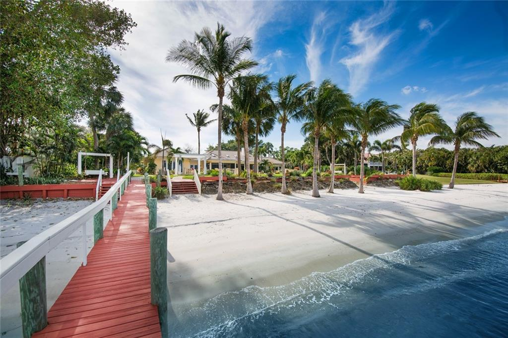 This property will make you feel like you own your own private resort! Take a swim in the pool, unwind in the spa, relax on a swing with a good book, launch your kayak from the white sandy beach or hop in your boat for a sunset cruise or off for a day of fishing! Imagine coming home every day to this tropical vacation lifestyle with 148 feet on the wide river.  Love to cook? The kitchen is designed to make your culinary creations a breeze with a 6 burner, gas Viking stove, lots of open prep space & storage, custom cabinetry and pantries. There are 2 master suites, one at each end of the home, that open out to the peaceful backyard and overlook the wide river. Completely renovated and expanded in 2008 with a grand foyer, living and dining area, a family room off the kitchen, spacious guest bedrooms and baths plus large screened patios, poolside decks and manicured garden paths. Enjoy all this property has to offer in the desirable Snug Harbor community with marina, tennis and clubhouse.
