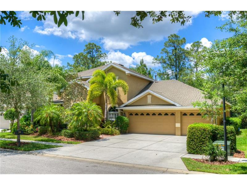 """Sensational new listing on a beautiful tree lined street in the heart of Tampa Palms. This remodeled home has it all! It offers 4 bedrooms, bonus room, office, 3 1/2 baths and 3 car garage. You will be immediately impressed with the canopy of lush mature landscaping, leaded front doors and transom window accents. The home offers a grand foyer with soaring ceilings that opens to the great room area. The kitchen and family room have a light, bright open feel and offer sweeping views of the pool and conservation. The kitchen is a chef's dream. It features quartz counter tops, 42"""" Cherry cabinetry, center island workstation, custom back splash, wine rack and stainless steel appliances that include a French Door Samsung refrigerator. Upgrades abound with exquisite tile floors, thick baseboards, column accents and deep crown molding. The staircase is a focal point with its iron spindles and hardwood steps. The first floor master suite offers hardwood flooring, tray ceiling, crown molding and plantation shutters. Enjoy the lavish feel of the master bath with marble counters, his/her sink and relaxing garden tub. The second floor has a large bonus room with wood flooring and 3 bedrooms with 2 full baths. Upscale finishes throughout the home include crown molding, designer light fixtures, plantation shutters and custom closet systems. Enjoy the tranquility of the conservation views from the spacious lanai. It features a large covered area, upgraded pavered deck and pool with a relaxing waterfall. Welcome home."""