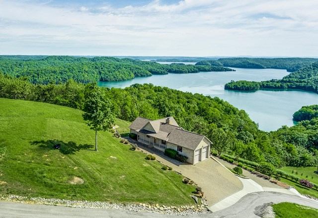 MINT Condition all brick home with an UNBELIEVABLE MAIN CHANNEL VIEW OF DALE HOLLOW LAKE.  This 3000 sq. ft. home is poised elegantly atop Swan Ridge Resort with a wide open view on 1.76 acres.  Exterior features also include two driveways designed with stone paving, interlocking block retaining walls, special garden area, upper and lower deck made with trex decking materials, and both decks have the same majestic wide open view of Dale Hollow Lake.  Interior features include 4 BR's and 3 full baths.  Main level has a master suite with full size walk in bath with gorgeous custom tile shower.  Just off the suite on the deck is a six person hot tub.  Living space is open-dining with stone fireplace.  The fireplace is EPA approved (Fireplace Xtrordinair) heats up to 3000 sq. ft., controlled heat, and draws air from the garage.  The kitchen flowing effortlessly has custom built Hickory cabinets and beautiful counter tops and island bar seating.