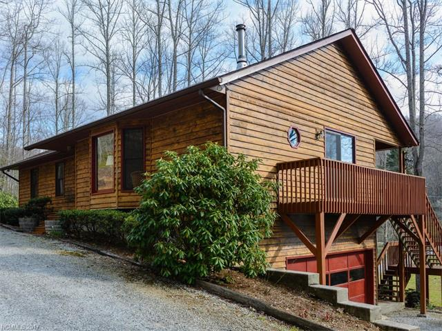 Wonderful private 3BD/3BA mountain home on almost 6 acres ,great Asheville access. Sale includes 4 lots! Lower land w/ 2 springs & creek offers opportunities: farming, gardening, a pond or just enjoy its beauty & mountain views from the decks nestled above the hardwoods & mountain laurel. A spacious, open home, kitchen island,large living room,wood stove & dining area.  Spiral staircase leads to the lower level & 2 car garage. lower finished Space not included in homes square footage.