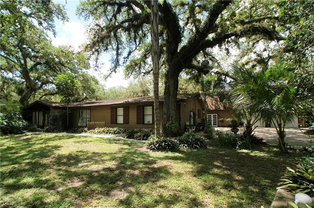 This beautiful home might be for sale, but it is the LIFESTYLE you are really buying. Nestled in a small development, secluded among large oak trees and surrounded by the State preserve featuring a large variety of wildlife wandering the 2.5+ acre grounds. Lined along the North Fork of the St. Lucie River (10 Mile Creek) a new journey begins with ocean access, unlimited fishing and amazing otters and manatees swimming by. The home features 3 spacious bedrooms, 2 full baths, formal living/dining area with three-sided fireplace. Along with an attached 2 bedroom, 1 bath in-law suite featuring its separate entrance into a living/kitchen room. There is a 10x10 shed with A/C. The two-story detached garage offers a large 2-car garage, open boat garage and a storage room with stairs leading to the 2nd floor. The 2nd floor is approximately 1200 sq.ft. and is open and ready to be finished. Minutes to I95, Turnpike, shopping, downtown and the beaches.  This secluded home is a hidden treasure!