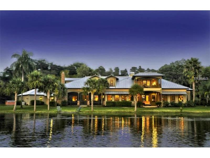 Gracious, Warm, and Inviting...Make memories that will last a lifetime in this private gated lakefront estate, masterfully designed by Thomas Lamb, on 70 acre ski Lake Brant, just north of Avila, and only 20 minutes to downtown Tampa!  Enjoy lakefront views from almost every room of the Magnificent Main Home, featuring 6,054 sf with 5 bedrooms, 4 1/2 baths, study, bonus, 3 car garage, and lots of charming covered porches created for savoring spectacular sunsets and carefree outdoor living.  Additional Carriage House features 1,046 sf with 2 bedrooms, 1 bath, full kitchen, living room & dining room and its own garage-perfect for extended family, guests, or live-in household help. Splendidly crafted, this home exudes charm and superlative attention to details, high pitched metal roof, and 1,000 sf lanai with wood burning fireplace, creating the perfect ambiance for the home\'s lakeside setting.  Impressive interior finishes including thick crown and dental moldings, antique wood ceilings, solid walnut wood floors, paneled wood & stack stone walls, custom cabinetry. Like boating and jetskiing? You\'ll enjoy a rustic boat house with covered boat lift & concrete floating dock, another gracious setting for family gatherings & fun! This amazing estate also includes a lighted, multi-purpose court for tennis & basketball.  This one of a kind home has something for everyone, is perfect for hosting special gatherings, enjoying the water, nature, and sunsets, and creating memories that will last a lifetime!