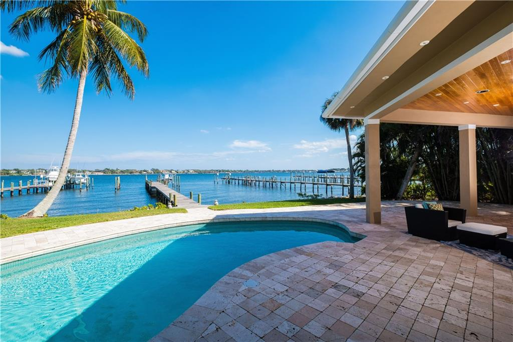 Stunning wide riverfront estate on the St. Lucie River is just minutes to the inlet by boat.  Large covered patio areas and a floor plan that flows indoors and out, make this an excellent home for entertaining and daily living, South Florida style!  Extensively remodeled, this home is in excellent condition and ready to move-into.  With plenty of glass (Andersen Impact windows and doors) to take in the full river views the home is also very energy efficient with an extensive solar Photovoltaic system installed new in 2013. The Chef's kitchen is complete with gas cooking, a steam oven, wine cooler, double wall oven and additional refrigeration drawers.  Marble and wood floors in main living areas. Private setting with a gated entrance and a paver stone driveway that can accommodate plenty of cars, boats and even a motor Coach! Bring the toys, there is an air conditioned 4-car garage too! Conveniently located near the inlet, shops and town.  Enjoy all that South Florida living offers.