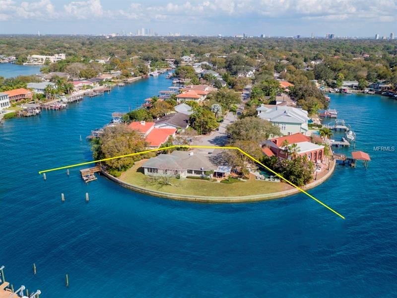 Overlooking the waters of Old Tampa Bay, this unassuming mid-century ranch sits on 260 feet of unrivaled open waterfront at the very end of the canal.  The property is just over ½ acre.  This one-story home is 3988 SF with 4 bedrooms and 3.5 bathrooms and offers an open floorplan with limitless options for living.  The kitchen and bathrooms have all been professionally renovated.  The home is filled with natural light and all back windows take in the surrounding water.  The dock and davits are protected on the north side of the property and the pool/spa is situated to offer unobstructed water views and sunsets.  Tile and wood flooring can be found throughout with a fireplace and high ceilings to add a contemporary casual feel.  The outdoor space offers an open patio around the pool and a covered lanai.  The cul de sac street and location are very quiet and private.  This is the perfect marriage of tranquility and drama.  The sunsets will take your breath away!!!